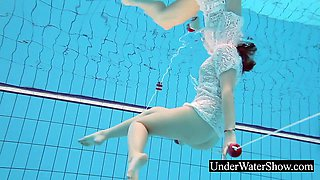 Slim redhead in the white dress underwater