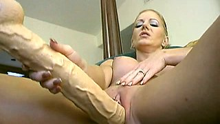 Fake tittied blond milf Amber Michaels digs her cunt with gigantic sex toy