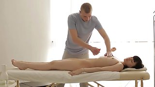 Handsome masseur lures naked brunette into sensual affair