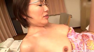 Mature Japanese MILF with glasses rides cock in a bra