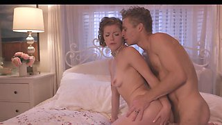 A couple is in the bedroom and they are fooling around together