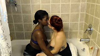 Interracial lesbian friends kiss each other in the bathtub