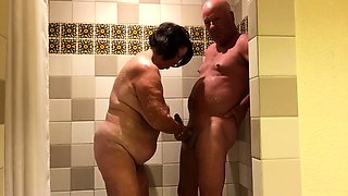 Big breasted granny sucks and strokes a cock in the shower