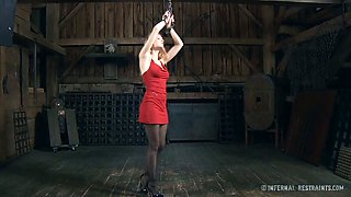 Lady in red is standing like a statue in this BDSM clip