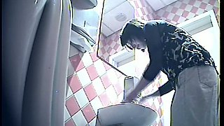 Brunette white lady in the public toilet room filmed from behind